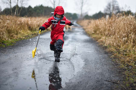 Young boy in a red coveralls with small shovel running through a paddle