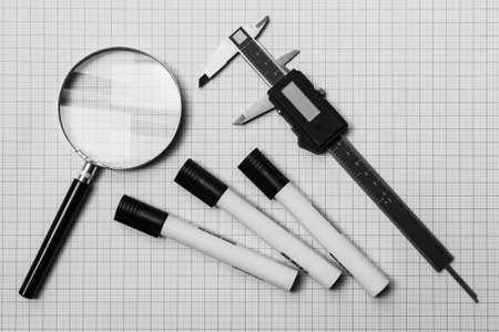 technic: Magnifying glass, electronic slide calliper and pens on a graph paper
