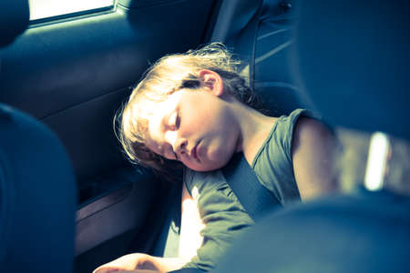 Little girl slepping on car's back seat