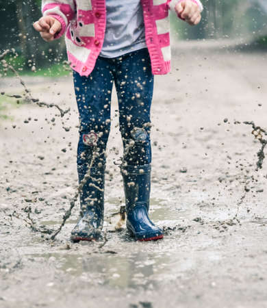 rainwear: Little girl in wellington shoes jumping in a paddle