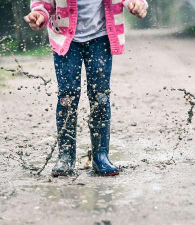 rainwear: Little girl in wellington shoes jumping in a paddle