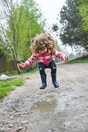 rainwear: Little girl in wellington shoes jumping in and paddle