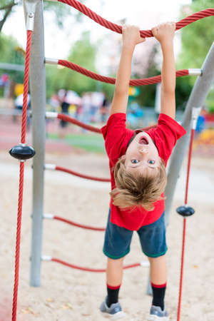 seven years: Seven years old boy hanging upside down on a rope Stock Photo