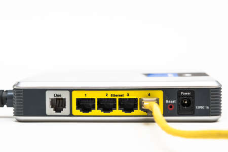 bandwith: A yelow ethernet cable connected to a network router isolated Stock Photo