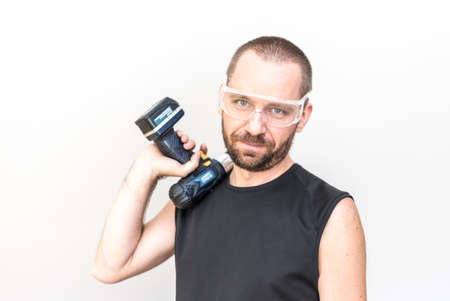 driller: Hansome worker in protection glasses holding a cordless driller on his shoulder Stock Photo