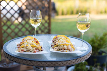 Glasses of white wine and mexican tacos dinner on a small backyard table