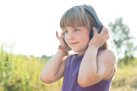 five years old: Cure five years old girl smiling and listening to music using black headphones Stock Photo