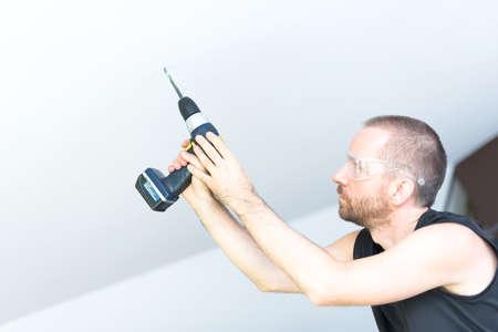 handsom: Hombre joven handsom la perforaci�n de un agujero en el techo blanco