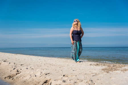 long skirt: Young woman with long blond hair wearing glasses and long skirt relaxing walking on a beach