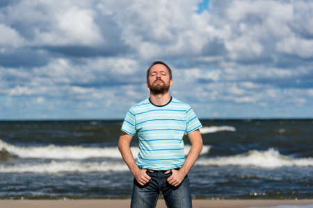 sea life centre: Young man with closed eyes and a beard contemplating on a beach during cloudy day and wrothful sea