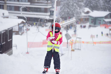 five years old: Five years old little skiing girl holding tight a handle of a ski tow Stock Photo