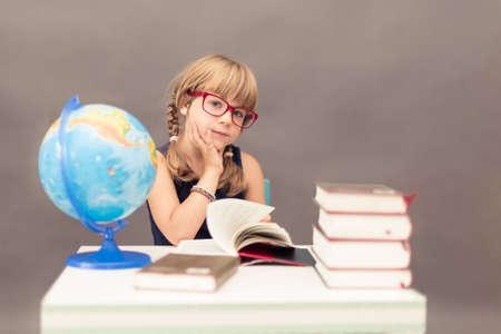 diligente: Colegiala joven que llevaba grandes gafas de color rojo en una mesa con libros gruesos y un globo