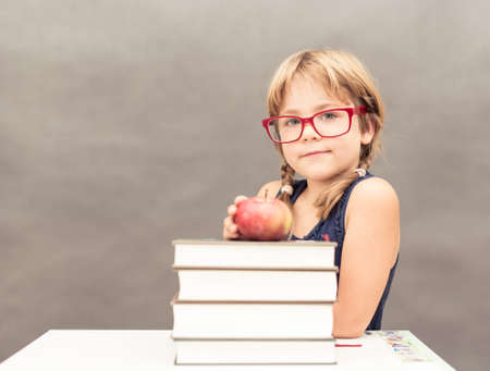 diligente: Colegiala con gafas jóvenes sentados en una mesa con una pila de libros gruesos y una manzana en la parte superior Foto de archivo