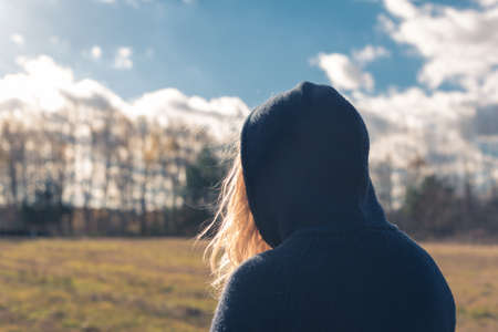shot from behind: A shot from behind a young girl with blond long hair wearing a hood walking in a park