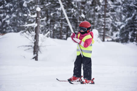 five years old: Five years old little skiing girl holding tight a handle of a ski tow Archivio Fotografico