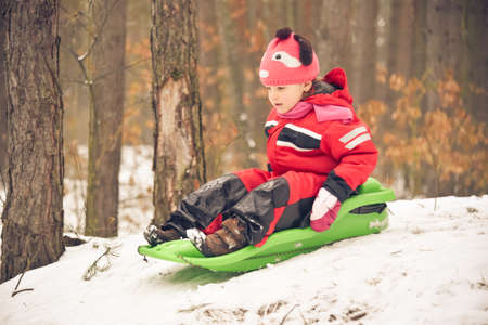 sledging people: Little girl wearing funny hat, black red white suit sliding down a small forest hill on her plastic sledge