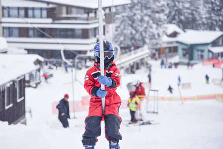 six years: Six years old little skiing boy holding tight a handle of a ski tow