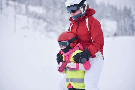 five years old: Young mother teaching her little five years old doughter skiing, girl wearing yellow jacket