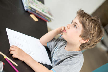 seven year old: Seven year old boy dreaming while doing his math homework