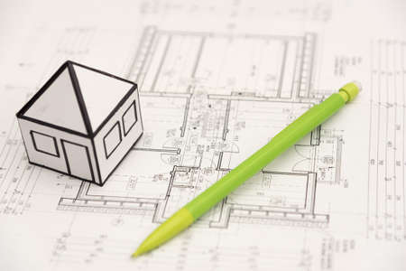 A pencil and little paper house on an architecture design drawings