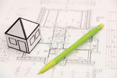 Ein Bleistift- und Papierhäuschen auf einer Architekturentwurfszeichnung