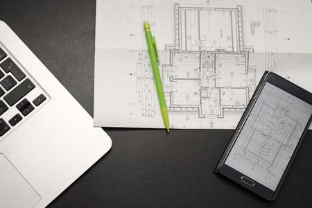 Laptop, smartphone, pencil and paper with drawings on a black desk - architecture design conecpt Standard-Bild