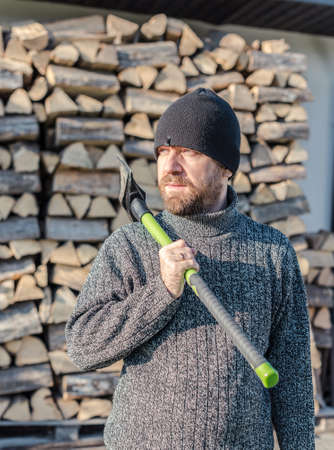 lumberman: Lumberman with an axe on his shoulder, stack of wood logs in background