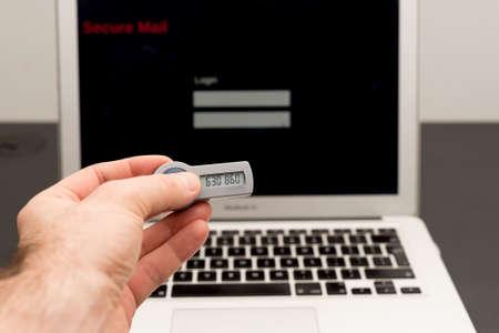 teclado num�rico: La mano del hombre la celebraci�n de un token seguro en frente de una computadora port�til y los registros en forma segura en l�nea Foto de archivo