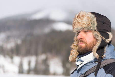 flaps: Bearded man wearing winter hat with ear flaps contemplating in a cold day