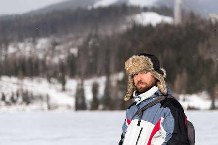 Brodaty mężczyzna ubrany czapka zimowa z nausznikami stojących w zimny dzień