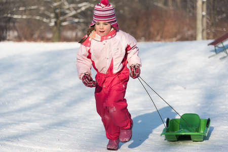 sledging people: Little happy girl running on snow pulling a sledge behind her Stock Photo