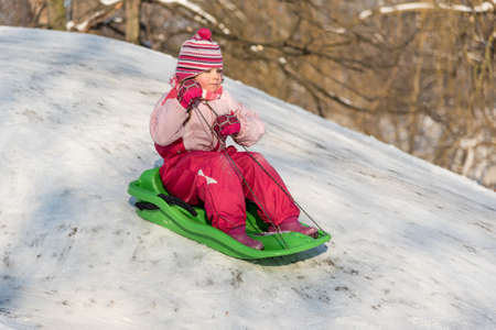 sledging people: Little girl on a sledge riding down a slope Stock Photo