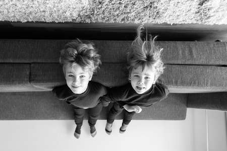 lying on back: Up side down shot of two little children lying back on a couch with heads hanging down