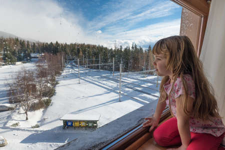 five years old: Five years old girl sitting on a sill and looking through a window at a sunny winter day