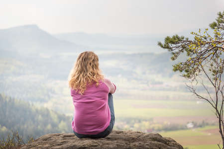 Woman with long blond hair sitting and contemplating on a rock in mountains. View  from her back with distant view blurred.