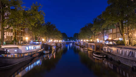 dimming: Boats moored along Amsterdam canals lit nicely by street lights with dimming deep blue sky reflecting in the water surface.