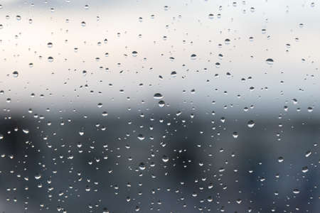 Rain drops on a wet window glass in a dark rainy day. Background behind completly blurred.