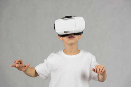 Young boy wearing virtual reality goggles controlling a game with his hands gestures