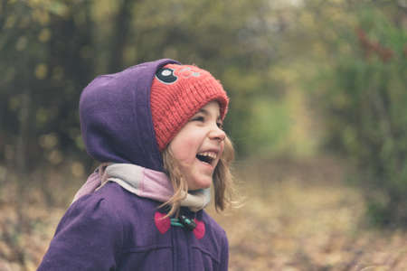 Little girl wearing red hat and purple jacket laughing on a autumn day