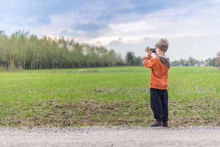 Young boy taking a picture of a landscape with his smartphone