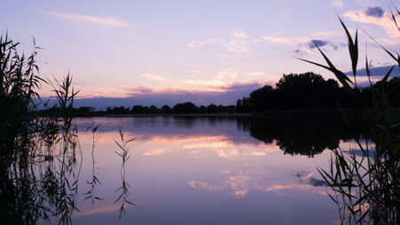 Purple sky and clouds reflecting in a surface of a lake after sunset with silhouettes of plants and trees. Lizenzfreie Bilder