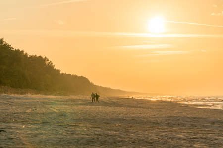 A couple of people in distance walking throug a sandy bean at sunset