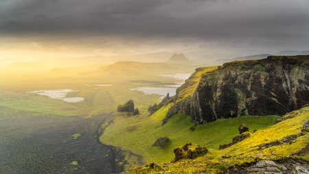 Rising sun iluminating icelandic hills and plains with its worm light