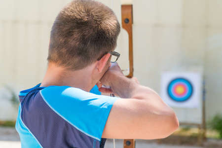 Young man wearing glasses aiming with a bow to a target, shot from behind