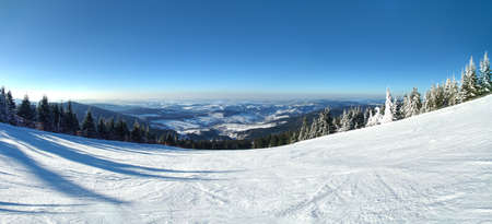 Panoramic view from Lysa Hora on a skiing trail with a little village Rokytnice nad Jizerou down the hill, Czech Republic Standard-Bild