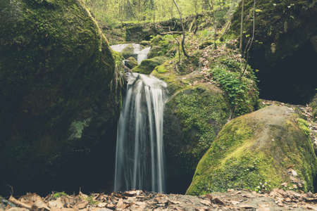 Small waterfall in a forest with huge rocks covered with moss Lizenzfreie Bilder