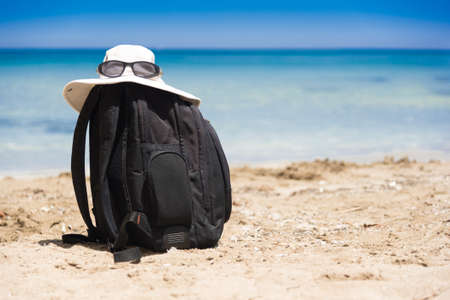 Sun glasses on white summer hat lying on top of a black backpack standing on a sandy beach at the sea