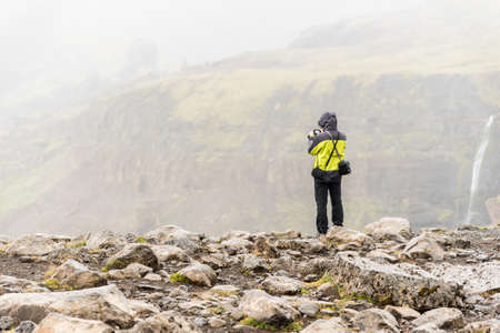 Man wearing a jacket with hood and photography equipment on his shoulders taking a picture of icelandic waterfalls with his digital camera
