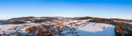 Birds eye view on a small village in mountains covered with snow in a sunny winter day
