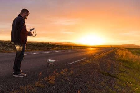 Junger Mann stand mit einer Fernbedienung vor seiner Drohne, die von einer Straße in einem frühen Morgen mit einer aufgehenden Sonne direkt über dem Horizont nahm Lizenzfreie Bilder